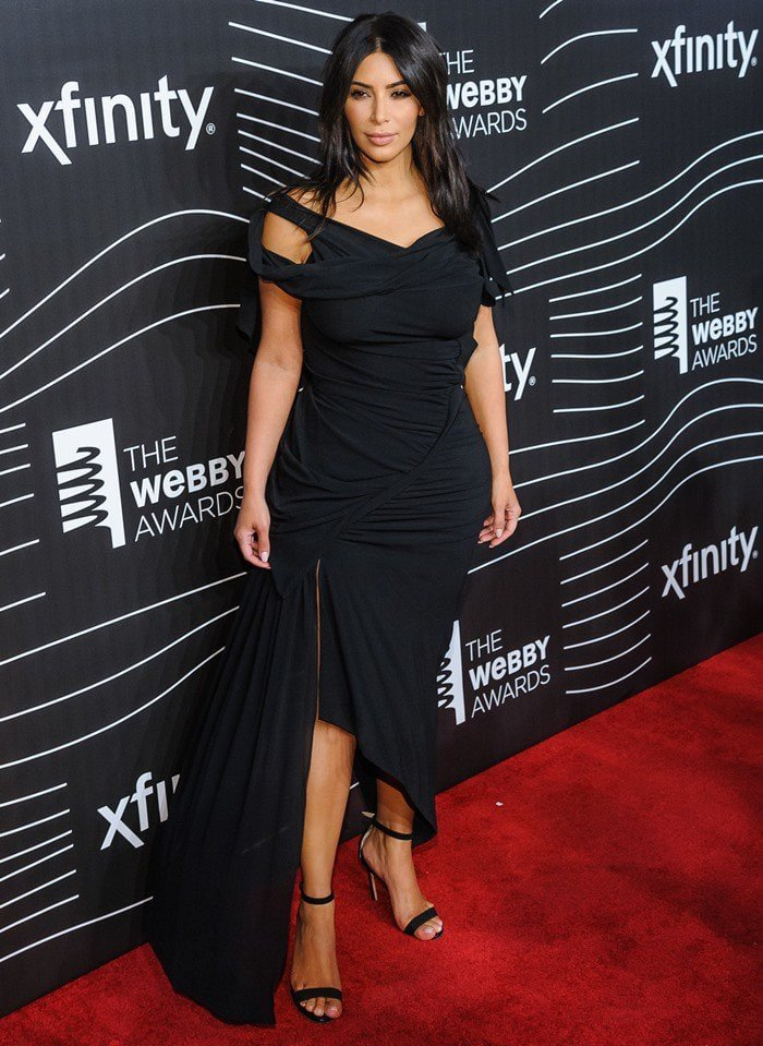 Kim Kardashian'sbody-hugging LBD was styled with a pair of open-toe ankle-strap sandals