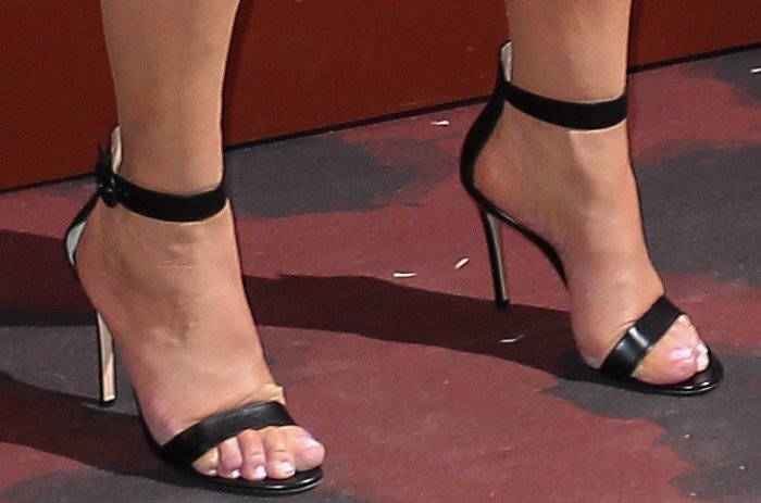 Kris Jenner's feet look uncomfortable in black strappy sandals
