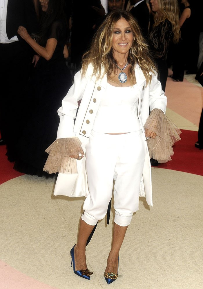 Sarah Jessica Parker wearing a white crop top with a nude lace-up corset at the back and tulle long sleeves
