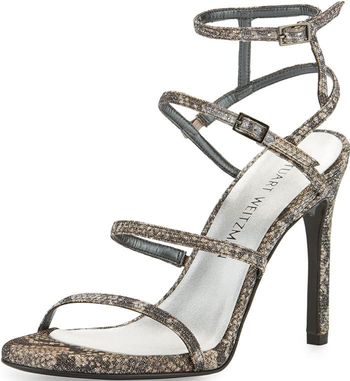 Delicate cage straps curve across a seductive stiletto sandal alight with a shimmering metallic finish
