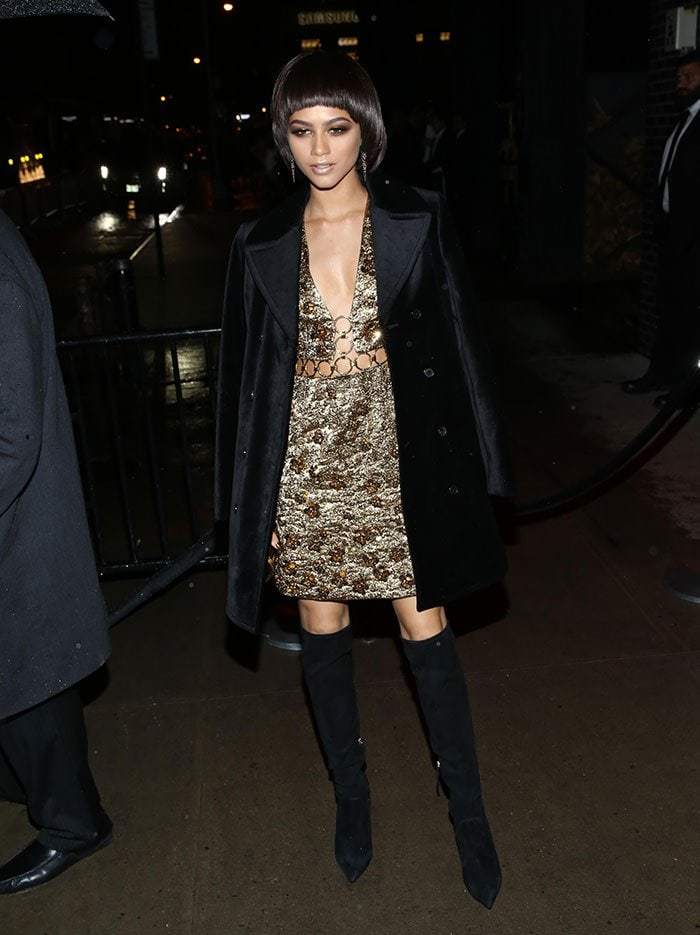Zendaya in a glittery short dress with a plunging neckline and a cutout across the midriff with gold hoop trims