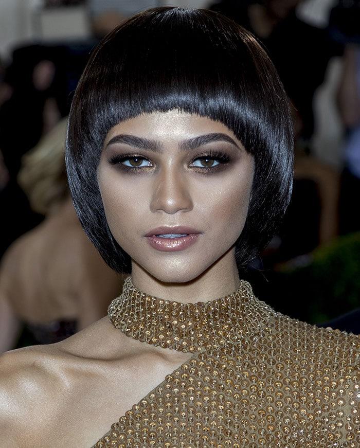 Zendaya sporteda futuristicbowl-cut wig, bronzed smokey eyeshadow, and glossy lipstick