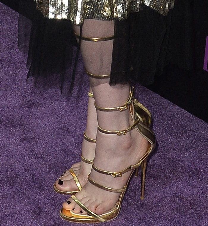 Bella Heathcote wearing strappy glossy gold leather Giuseppe Zanotti sandals