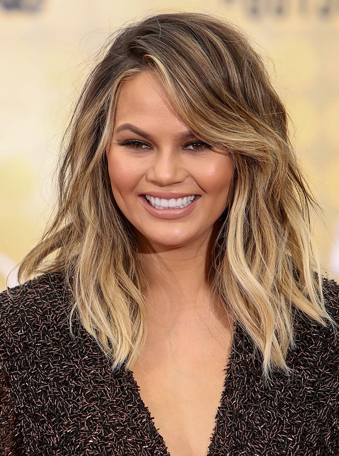 Chrissy Teigen'sside-parted wavy hairstyle and seductive nude makeup