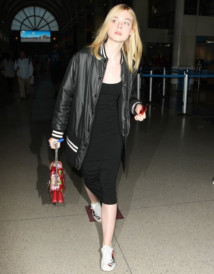 """Elle Fanning arrives at LAX in a black jersey dress, varsity jacket, and Gucci """"Ace"""" floral embroidered sneakers on June 23, 2016"""