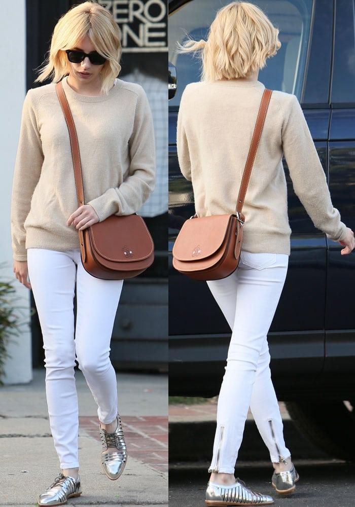 Emma Roberts rocked an AG Adriano Goldschmied Rylea crew sweater and white Rag & Bone zipper trim skinny jeans