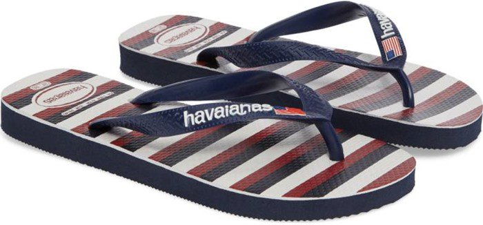 A small American flag graces the toe strap of a comfortable rubber flip-flop styled with a bold flag motif on the footbed