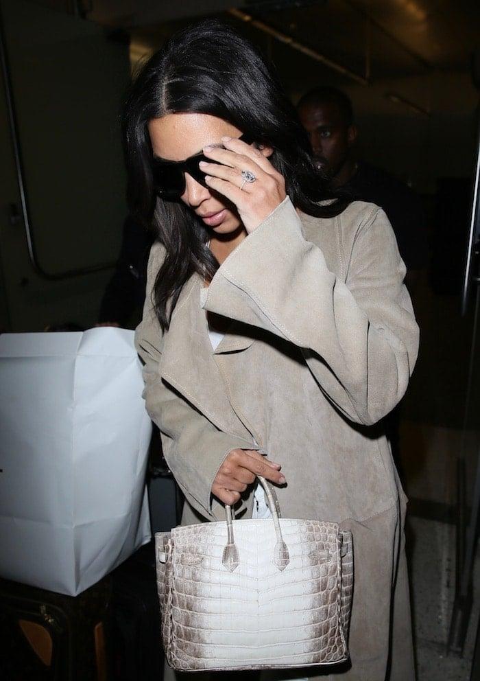 Kim Kardashian wearing a long, beige trench coat