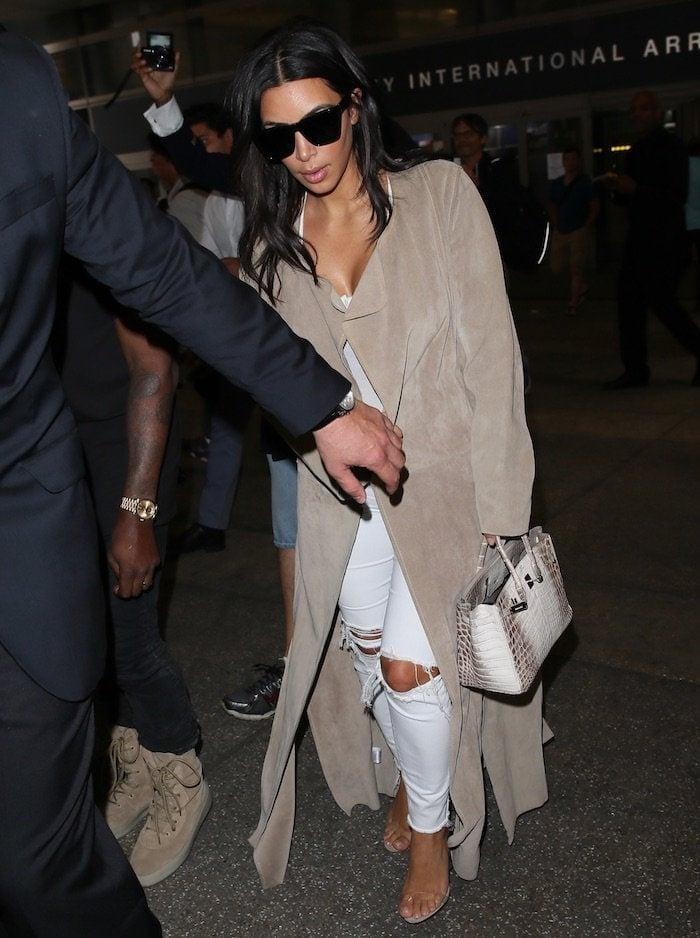 Kim Kardashian sporting J. Brand distressed jeans, a bodysuit and Yeezy Season 2 Lucite sandals