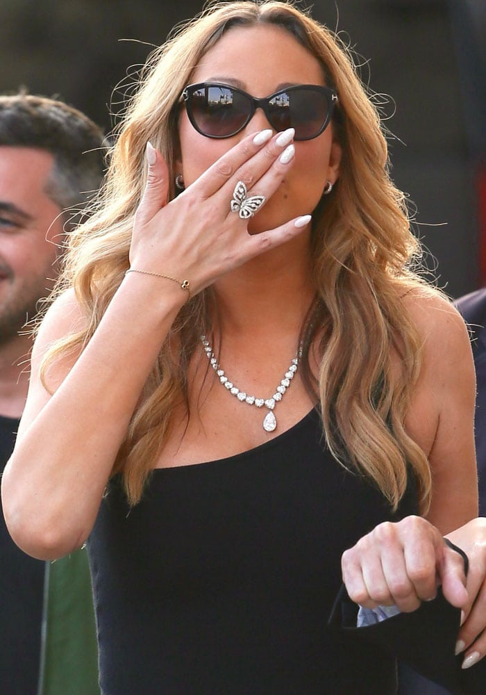 Mariah blows her awaiting fans a kiss with her butterfly ring-clad hand