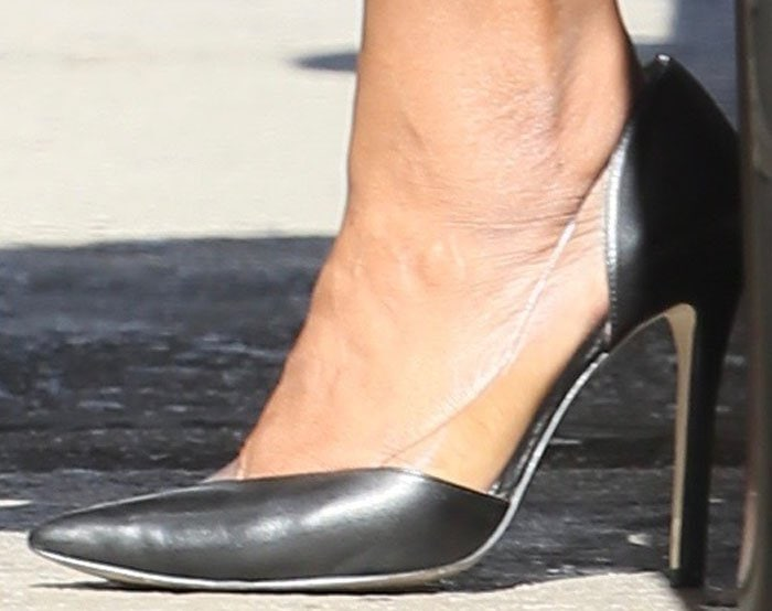 Mindy Kaling jumps out of her car in a pair of asymmetrical PVC leather pumps