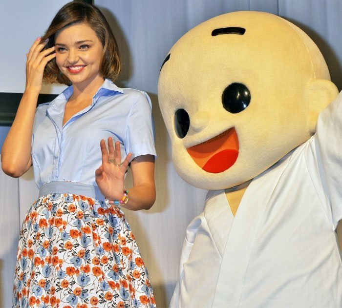Miranda Kerr poses with the mascot after putting on a simple cooking demonstration for the press
