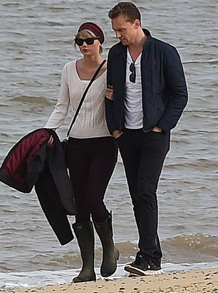 Taylor Swift clings on to her new man as they take a romantic stroll along the beach