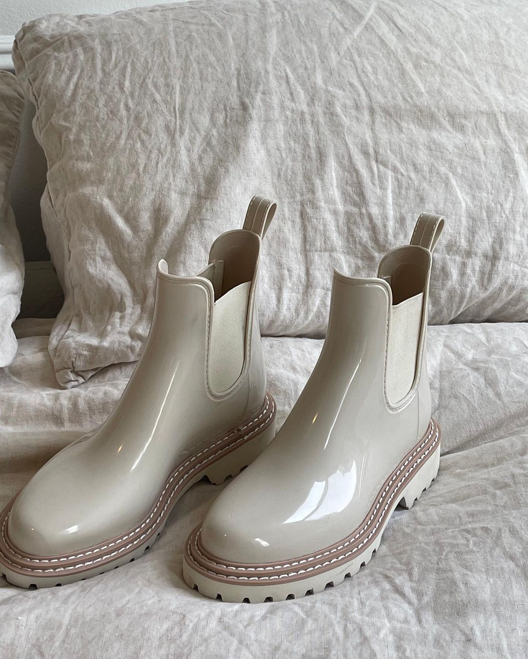 Ivory patent pull-on design rain boots with almond toe featuring rear pull loop and elastic gore panels for a secure, flexible fit