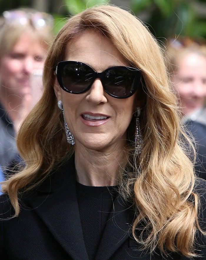 Celine Dion shows off her diamond dangle earrings