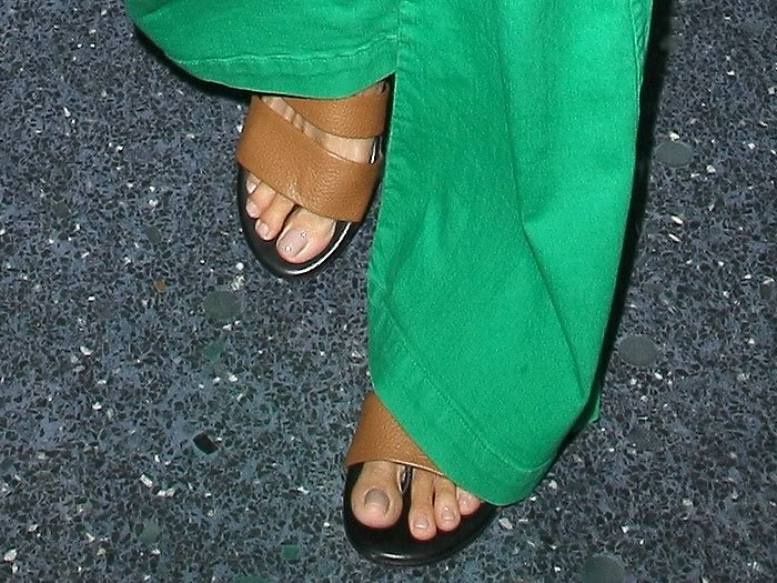 Heidi Klum's feet in two-band flat sandals with tan wide straps and black soles