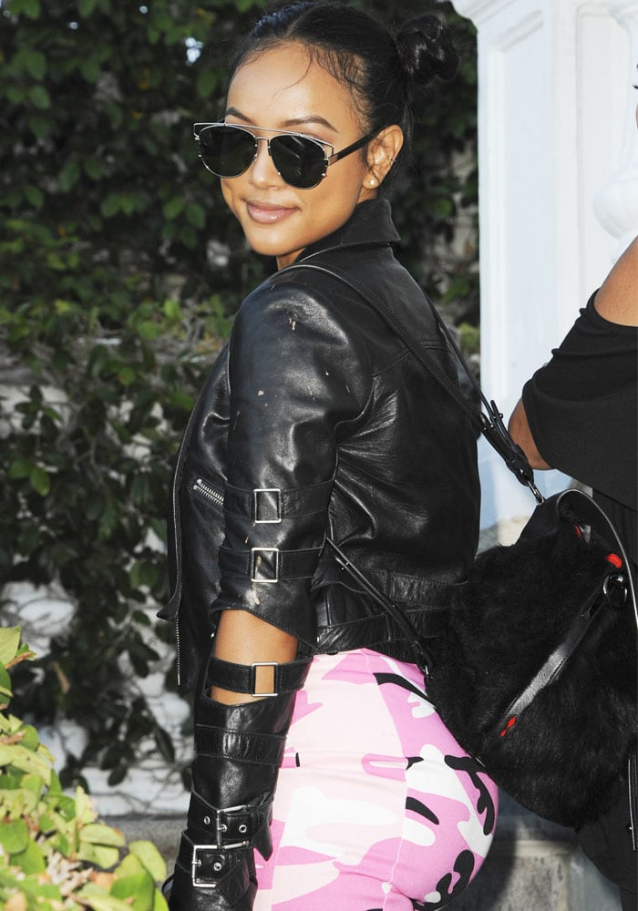 Karrueche Tran rockingDior-like sunglasses and a fuzzy black backpack