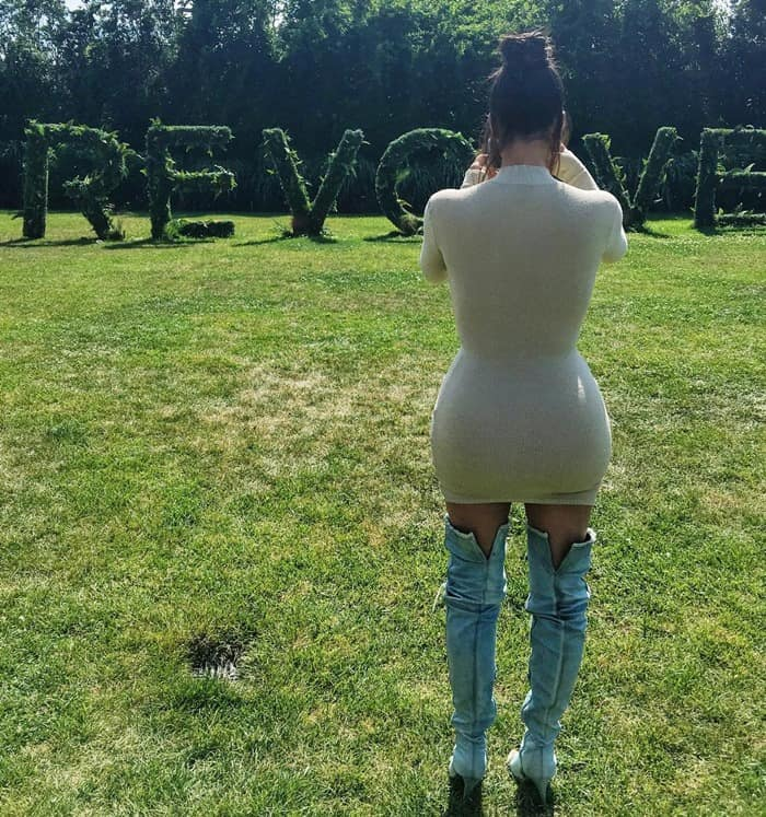 The back of Kim Kardashian's curvy form in a Trois x Revolve 'Campbell' beige knit dress and Yeezy ripped denim thigh-high boots