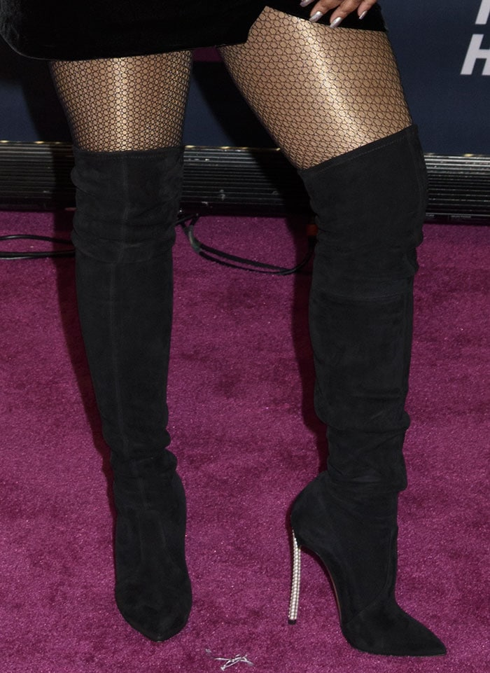 Lil' Kim added several inches to her height with over-the-knee suede boots