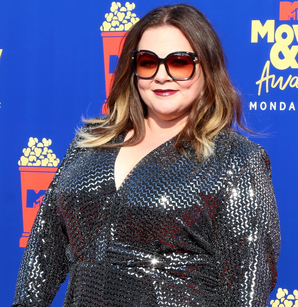 Melissa McCarthy rocks sunglasses with Dena Kemp jewelry and a sequined jumpsuit by Talbot Runhof