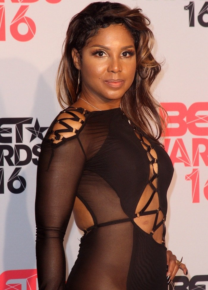 Toni Braxton's dress features cutout and sheer details as well as a large thigh-high slit