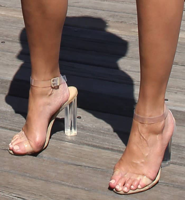 Chrissy Teigen wearing Kanye West's lucite heels