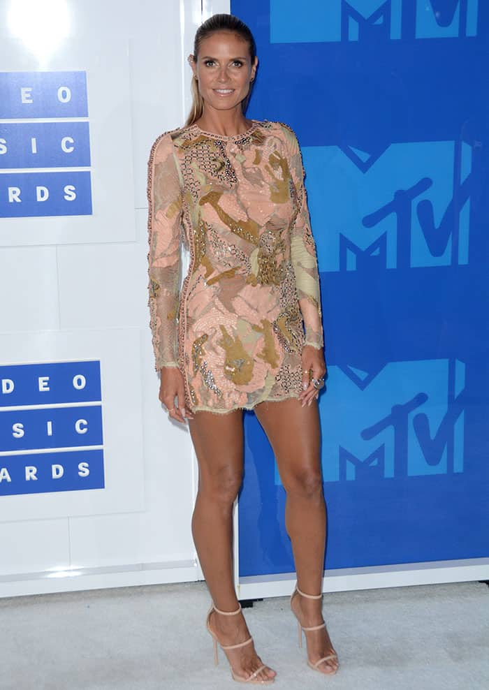 Heidi Klum flaunted her $2.2 million insured legs in an intricate blush dress