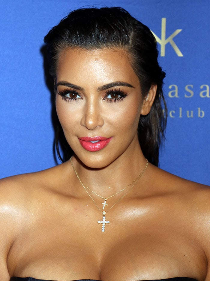 Kim Kardashiansported pink lipstick and wore her hair in a slicked-back style