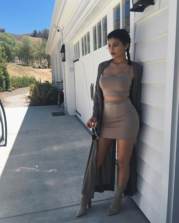 Kylie Jenner's Instagram posts of her monochromatic beige ensemble consisting of a Naked Wardrobe Walkin Thin Lines crop top and miniskirt set and Yeezy season 2 knit booties