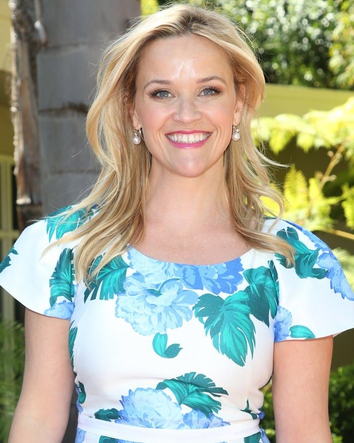 Reese Witherspoon wearing a flutter sleeve shift dress in peony print from her own Draper James label