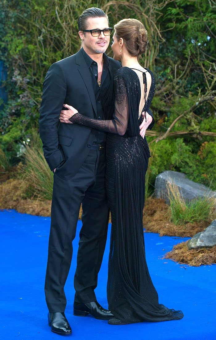 """Getting support from her man in an black Atelier Versace spring 2014 draped long-sleeved gown and black Christian Louboutin """"Fifi"""" strass pumps"""