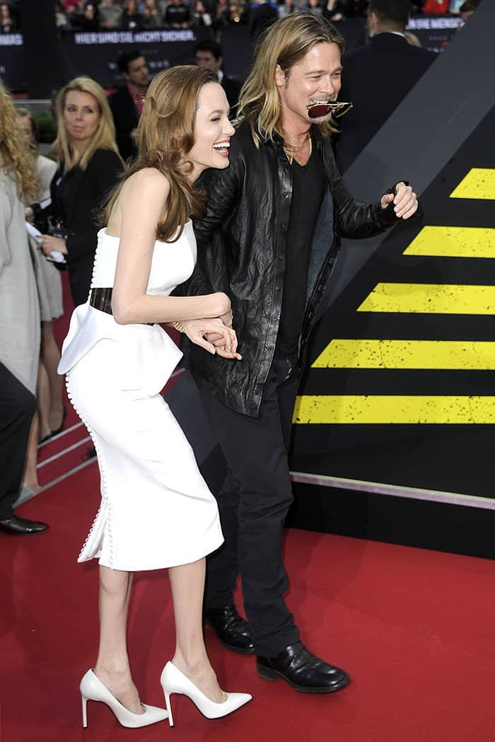 """Sharing a laugh in a white Ralph & Russo sculpted-peplum strapless dress and white Saint Laurent """"Escarpin"""" pumps"""