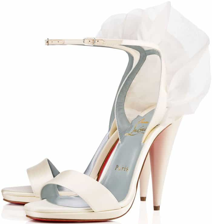 Wispy wings fly at the heel of a striking ankle-strap sandal lifted by a architectural cone heel