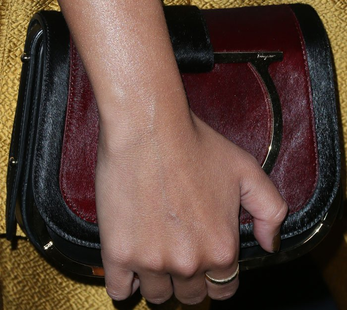 Emily contrasts her gold outfit with a calf hair clutch by Salvatore Ferragamo