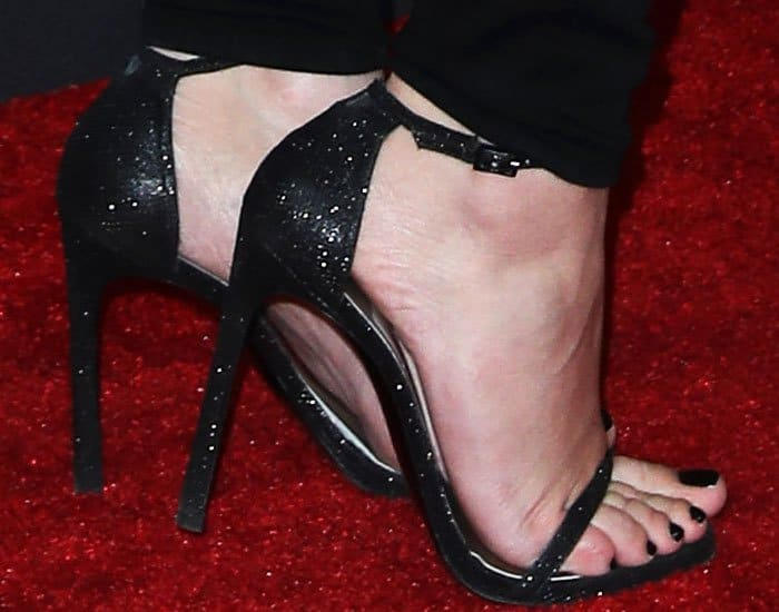 "Hailee Steinfeld's hot feet in classic Stuart Weitzman ""Nudistsong"" sandals in black glitter leather"