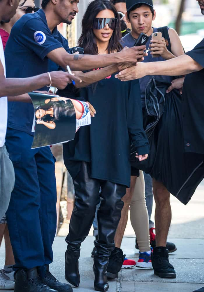 Kim stops to take photos with fans outside her New York apartment