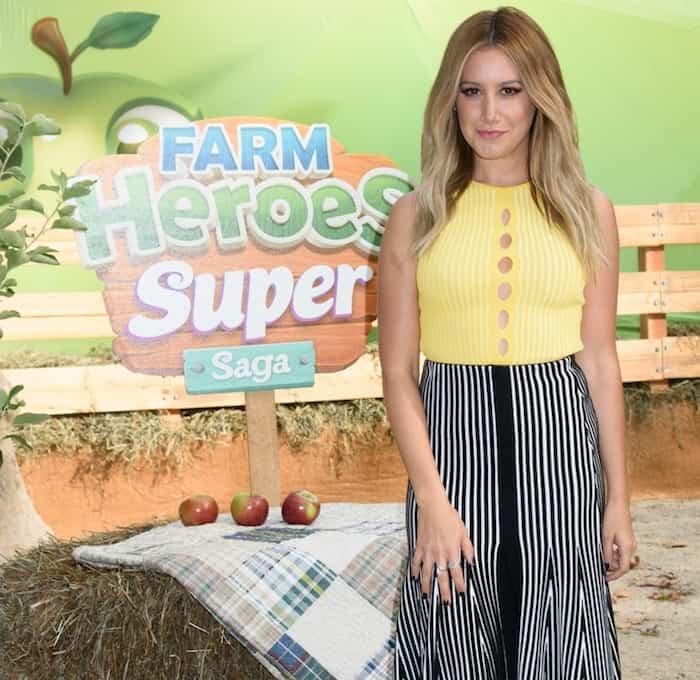 Ashley Tisdale rocks a pin-stripe midi skirt and a yellow cutout crop top