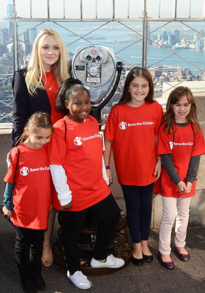 """Dakota poses with the children from""""Save the Children,"""" which is an organization that she champions"""
