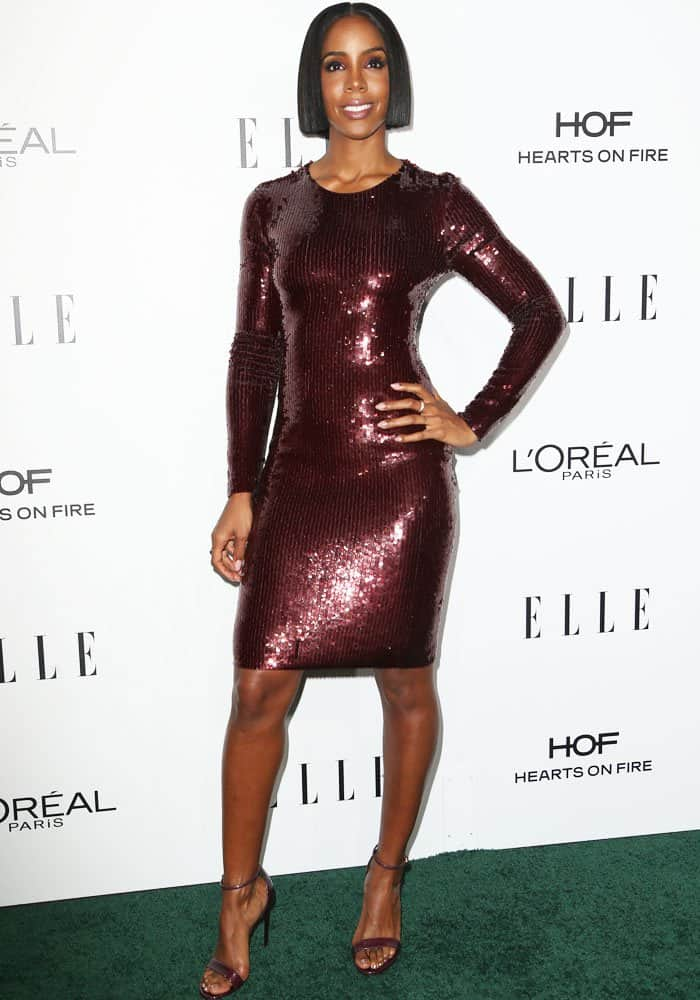 Kelly Rowland flaunts her legs in a burgundy sequined dress with a matching reptile print-embossed sandals