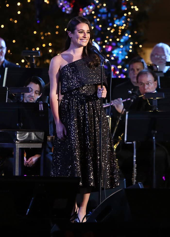 Lea Michele glistened in a gold-patterned black dress as she performed a few Christmas songs