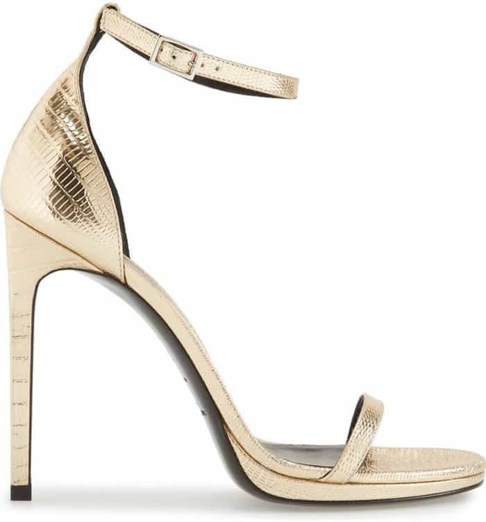 Skinny straps cast in alluring patent leather adorn a minimalist Saint Laurent sandal lifted by a chic stiletto heel