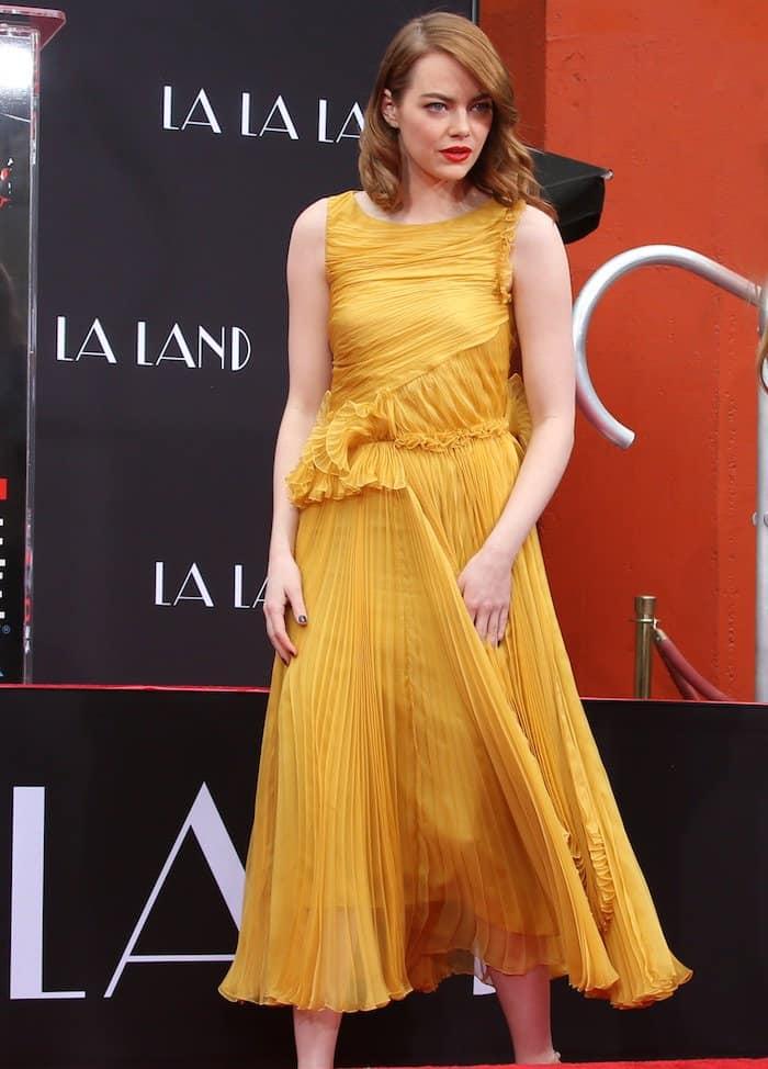 Emma Stonein a bright orange midi dress from Rochas' Spring 2017 collection