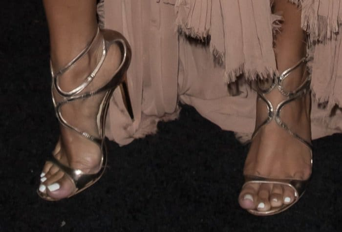 Karrueche Tran shows off her feet in wavy-strap sandals in bronze