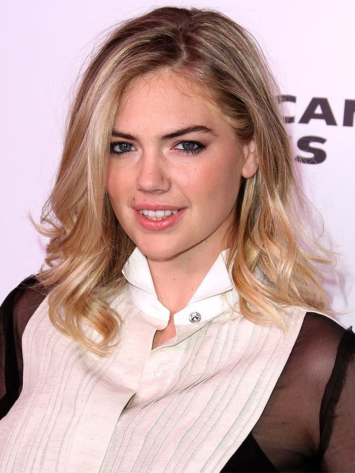 Kate Upton wears a sheer-sleeved tuxedo shirt sloppily unbuttoned at the collar