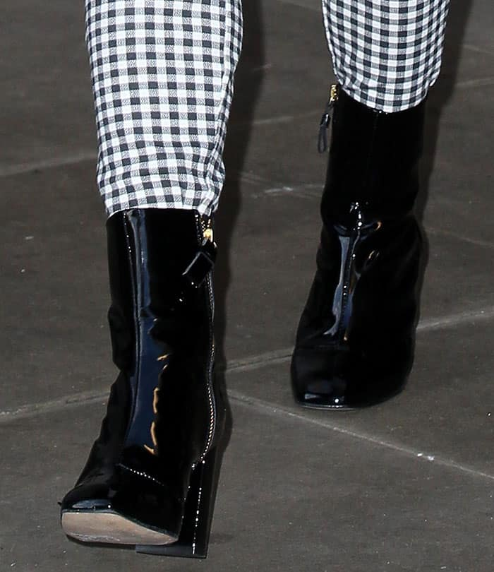 Maisie Williams in glossy patent boots