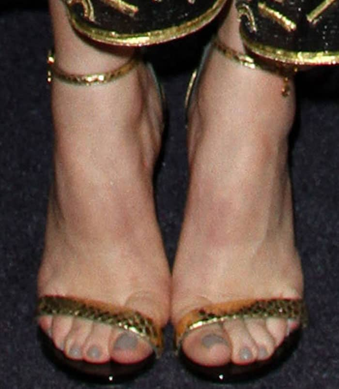 Peyton put on a golden look with a pair of Loriblu reptile print-embossed sandals