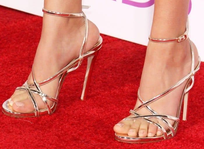 Victoria looks golden in a pair of metallic Stuart Weitzman sandals