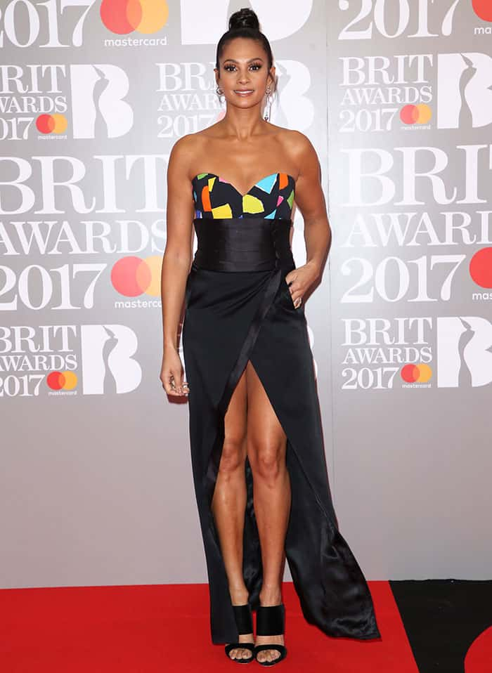 Alesha Dixon wearing a black Ronald Van Der Kemp wrap skirt, a colorful Moschino top, and Giuseppe Zanotti sandals at the 2017 Brit Awards