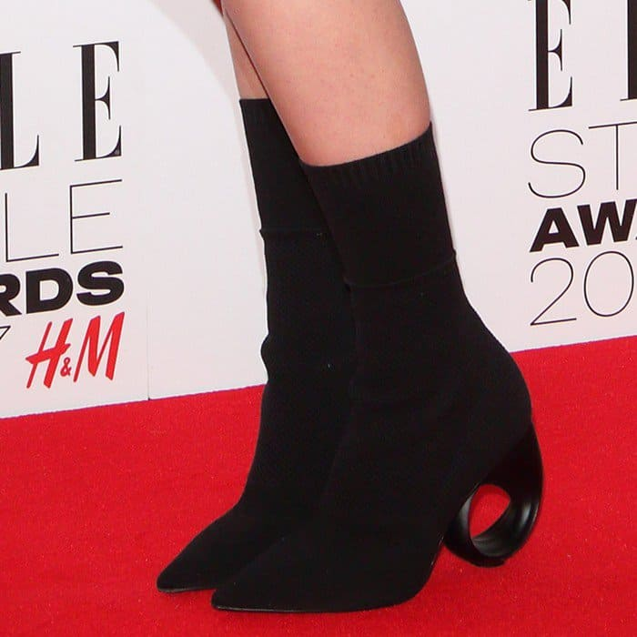 Anya wearing heeled ankle boots with circular cutouts
