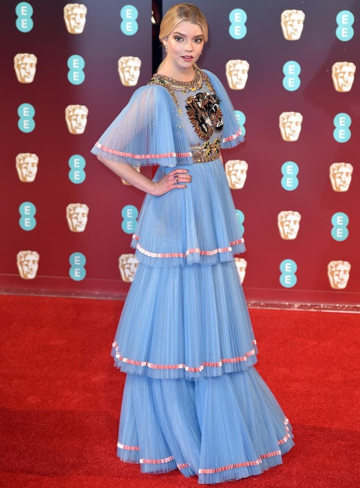 Anya Taylor-Joy in a powder blue Gucci gown featuring panther embroidery on the bodice, pleated layers, and rounded sleeves. Anya accessorized with Amrapali earrings